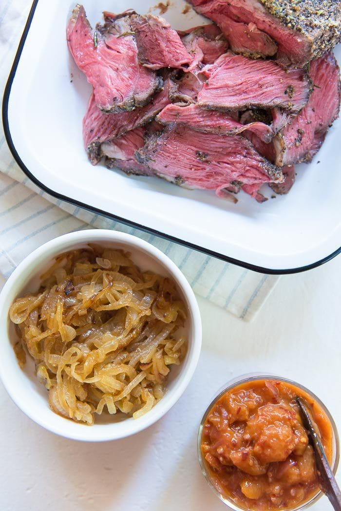 Slow roasted beef thinly sliced for steak sandwiches in an enamel tray. With other steak sandwich fillings like, caramelized onions in one bowl and spicy peach relish in another bowl.
