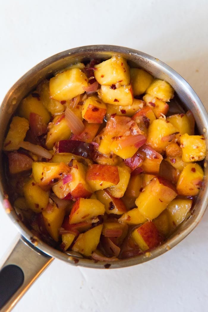 Fresh chopped peaches mixed with the relish spices, in a saucepan.