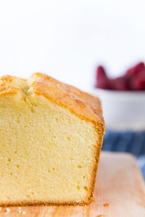 A close up look at the sliced pound cake. The crumb is close, but moist and soft, with a thin brown outer crust.