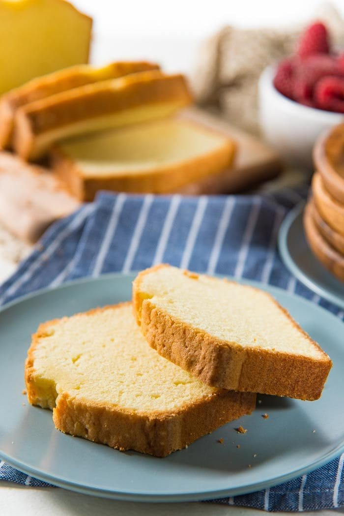 two slices of classic pound cake on a blue plate, with the rest of the pound cake, sliced, in the background. with a bowl of berries and more serving plates in the background.