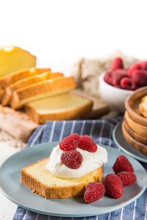 A slice of pound cake on a blue plate, served with a dollop of whipped cream on top, with fresh raspberries. A bowl of fresh raspberries, more sliced pound cake in the background.