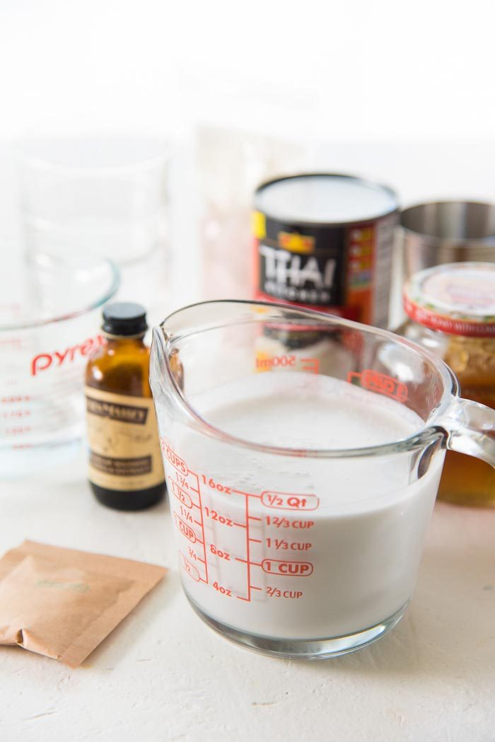 Ingredients for a coconut panna cotta on a white table top. Coconut milk in a jug, gelatin packet, vanilla, and honey.