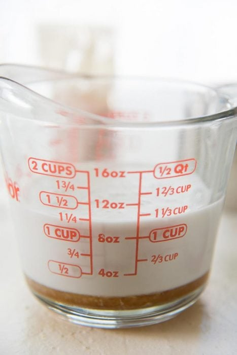 The coconut milk in a measuring jug with the honey at the bottom.