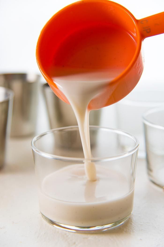 Pouring the coconut panna cotta into individual serving glasses using a measuring cup, to make sure each portion is even.