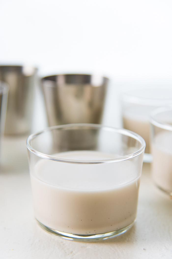 Paleo coconut panna cotta poured into individual serving glasses, and being allowed to cool at room temperature.