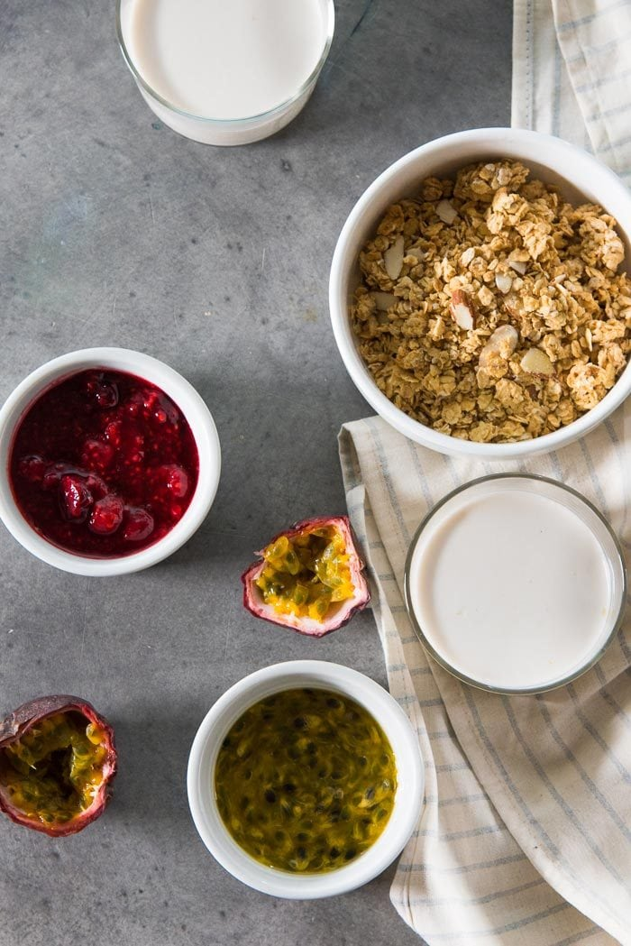 An overhead view of some coconut panna cotta glasses and passionfruit sauce, raspberry compote and granola in separate bowls.