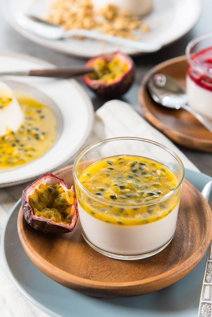 A Passion fruit topped Coconut panna cotta served in a glass, with half a fresh passion fruit next to it.