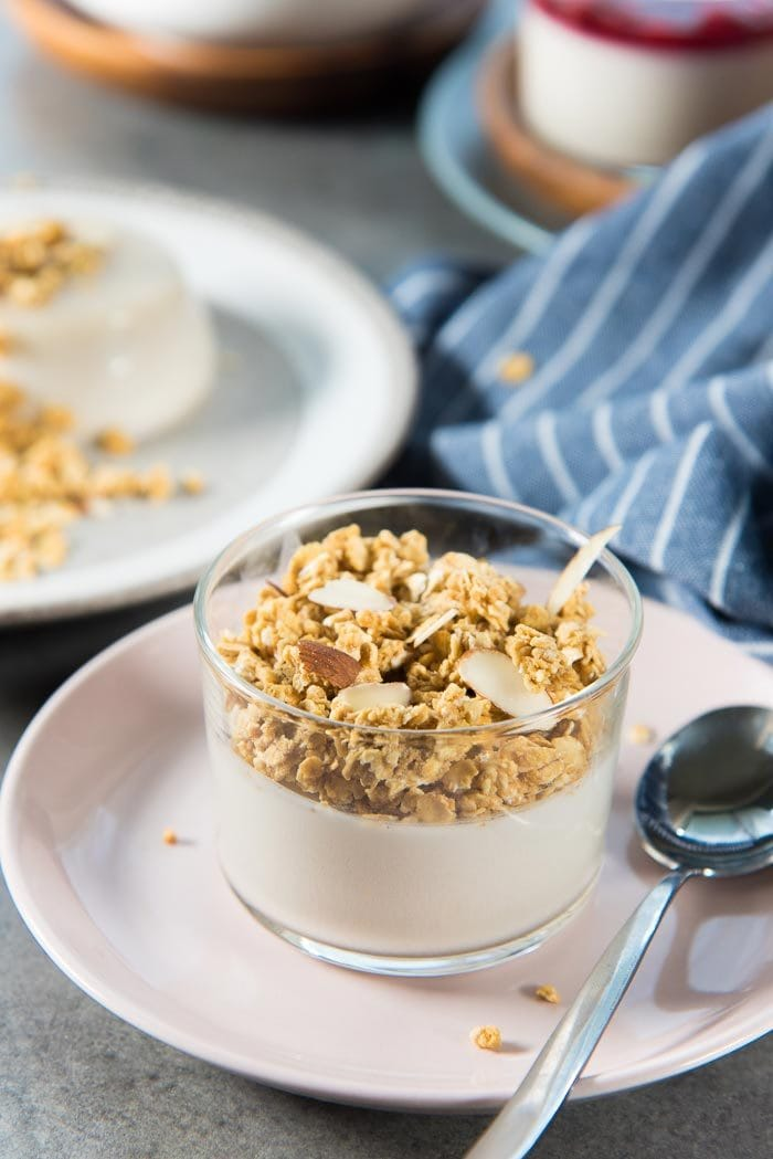 Paleo Coconut Panna Cotta served in a glass, topped with almond granola, on a baby pink plate. Perfect for breakfast.