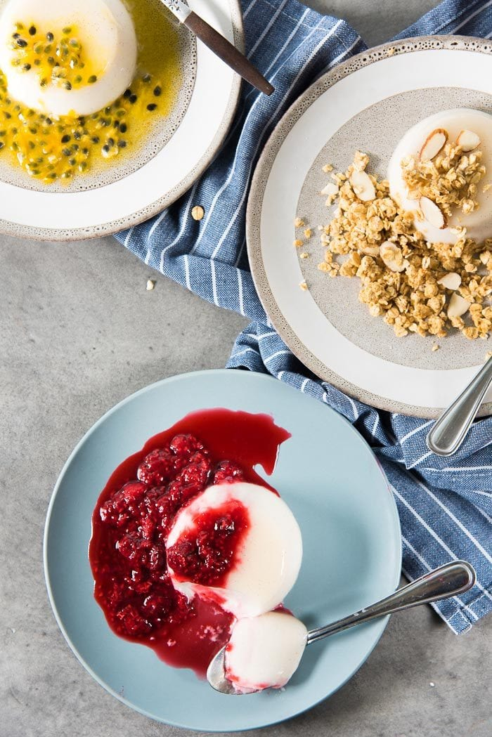 Easy coconut panna cotta served in 3 ways - over head view of coconut panna cotta served with raspberry compote, passionfruit syrup and granola.