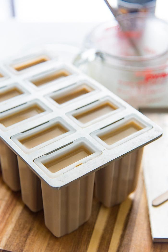 The coffee infused coconut milk has been poured into 10 popsicle molds. The popsicle mold is on the table allowing the popsicles to cool down slightly. These iced coffee and coconut milk popsicles should be allowed to thicken slightly (in freezer) before inserting the sticks.