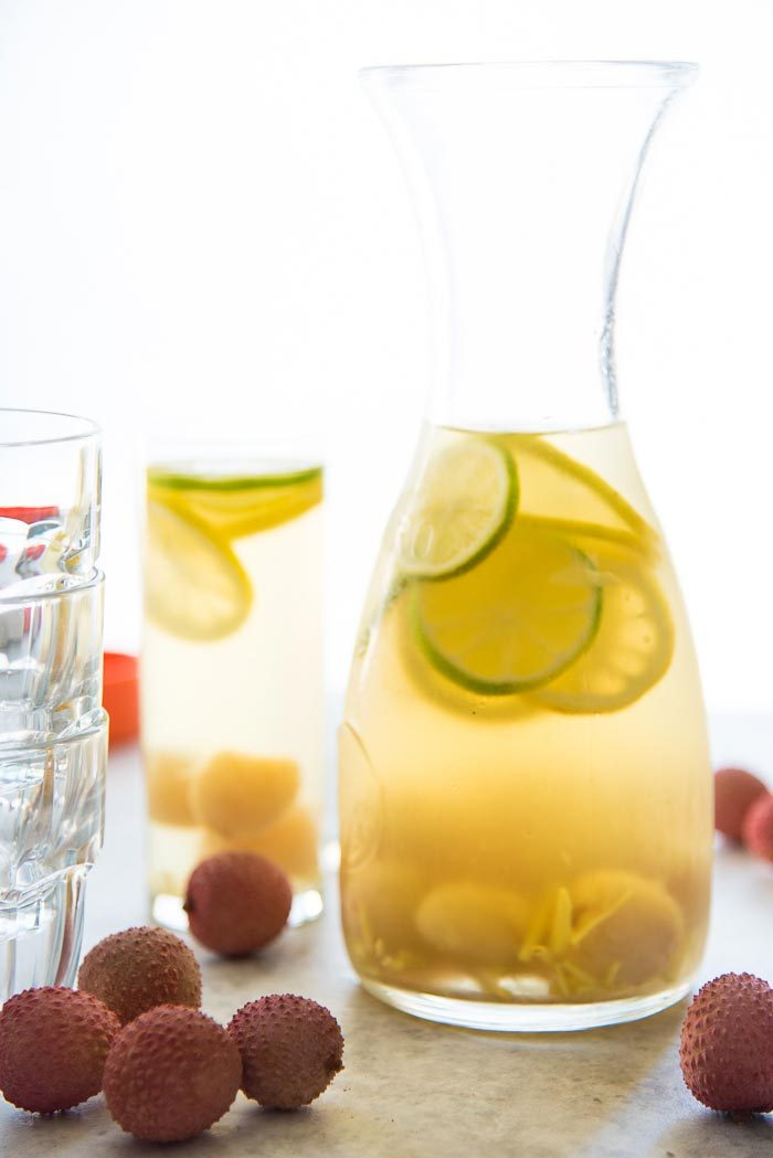 A carafe of Ginger lychee Sangria Blanca, with lychee, ginger pieces, lemon and lime slices.