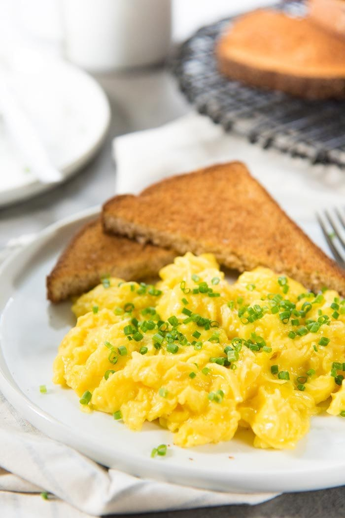 A close up to show how fluffy and creamy these perfect scrambled eggs are. Served on a white plate with chopped chives and toast.