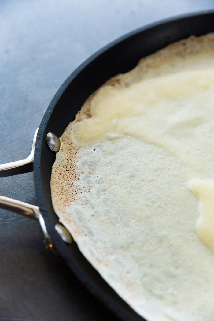 For basic crepes, wait for the edges to brown and crisp up slightly. Then it's ready to flip over (or ready to eat).