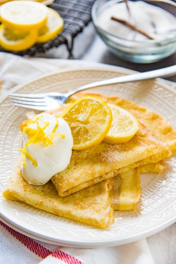A refreshing summer Lemon and vanilla sugar crepes dessert, on a plate. An easy dessert to whip together for guests.