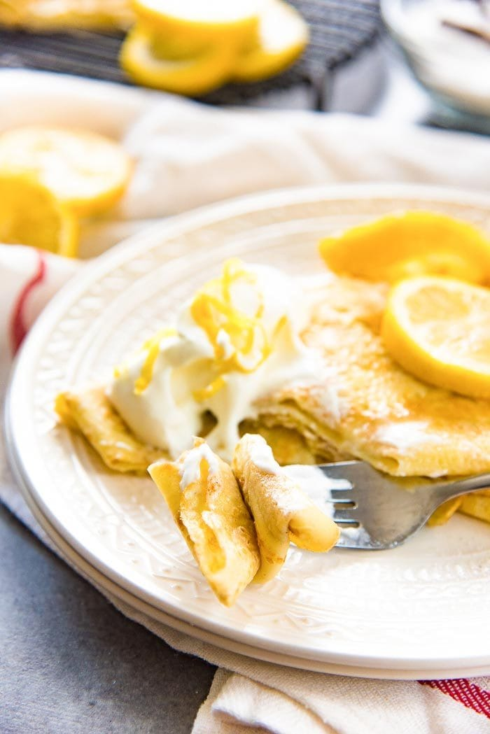 Soft crepes cut up on a fork, with whipped cream.