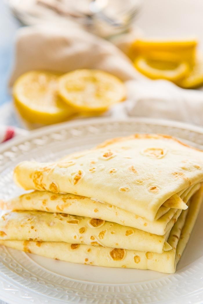 A stack of delicious crepes, folded over into quarters, on a plate.
