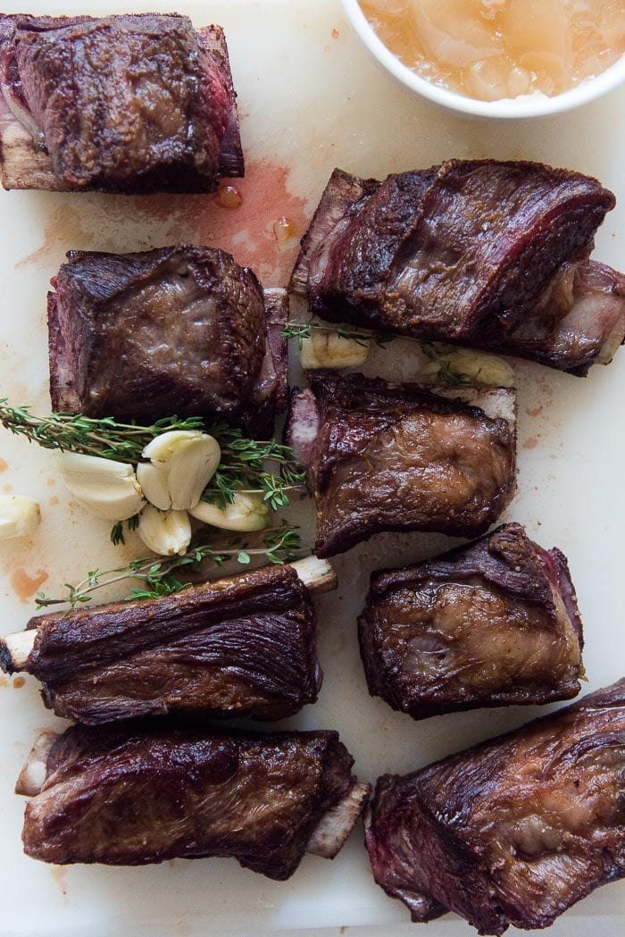 Short Ribs that have been seared and caramelized on a white board with whole garlic cloves and thyme.