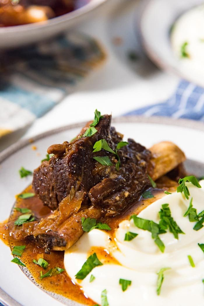 A close up of the braised instant pot short ribs with creamy mashed cauliflower with gravy on a plate.