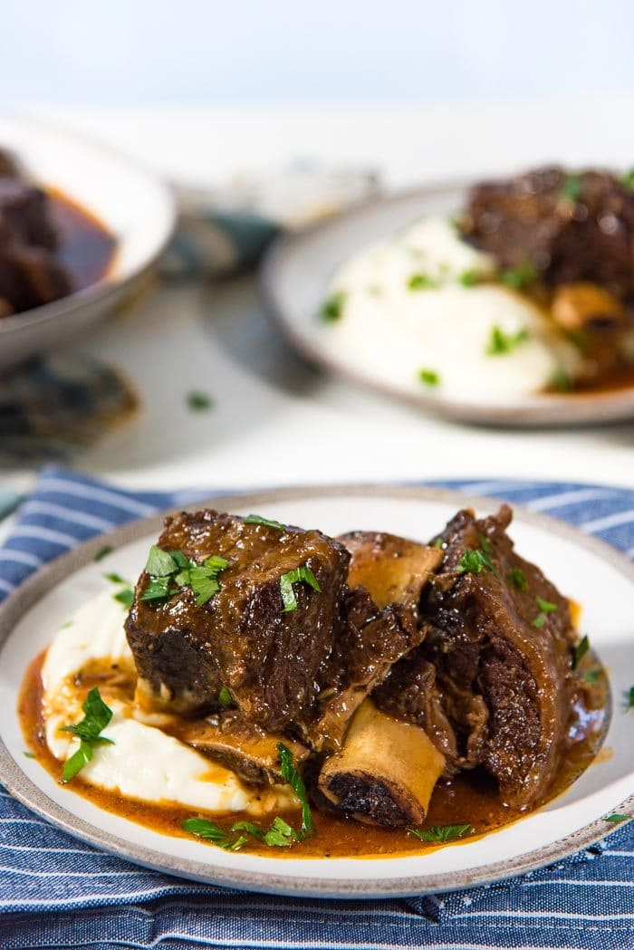 A serving of braised short ribs with no wine, served on a plate of creamy mashed cauliflower.