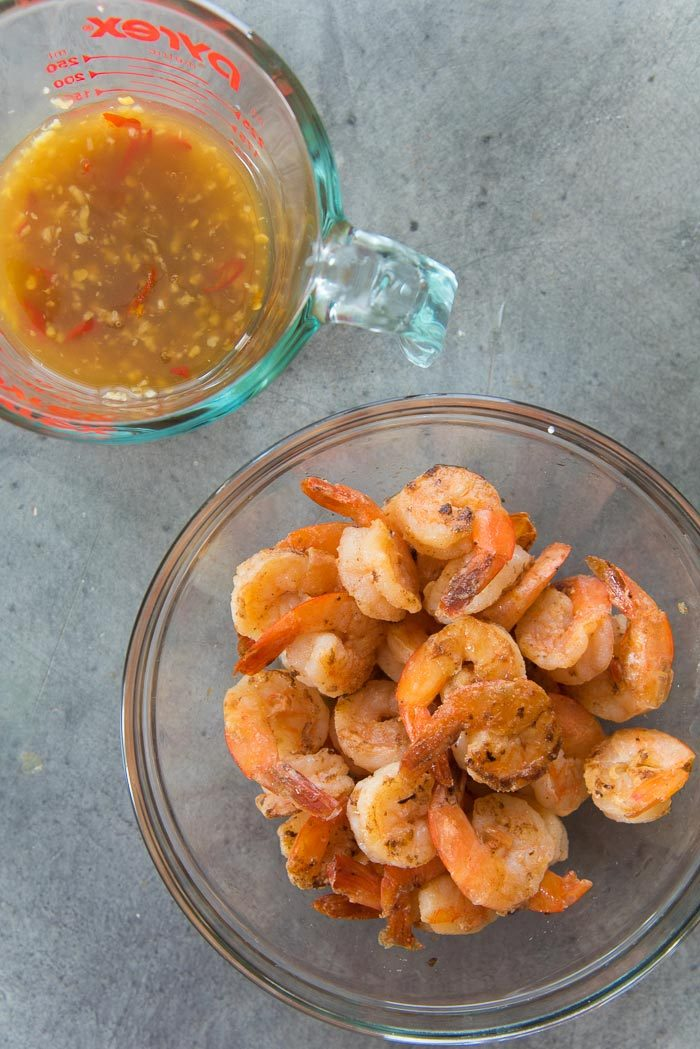 Grilled Shrimp in a bowl with the garlic lime sauce in a jug before mixing them.