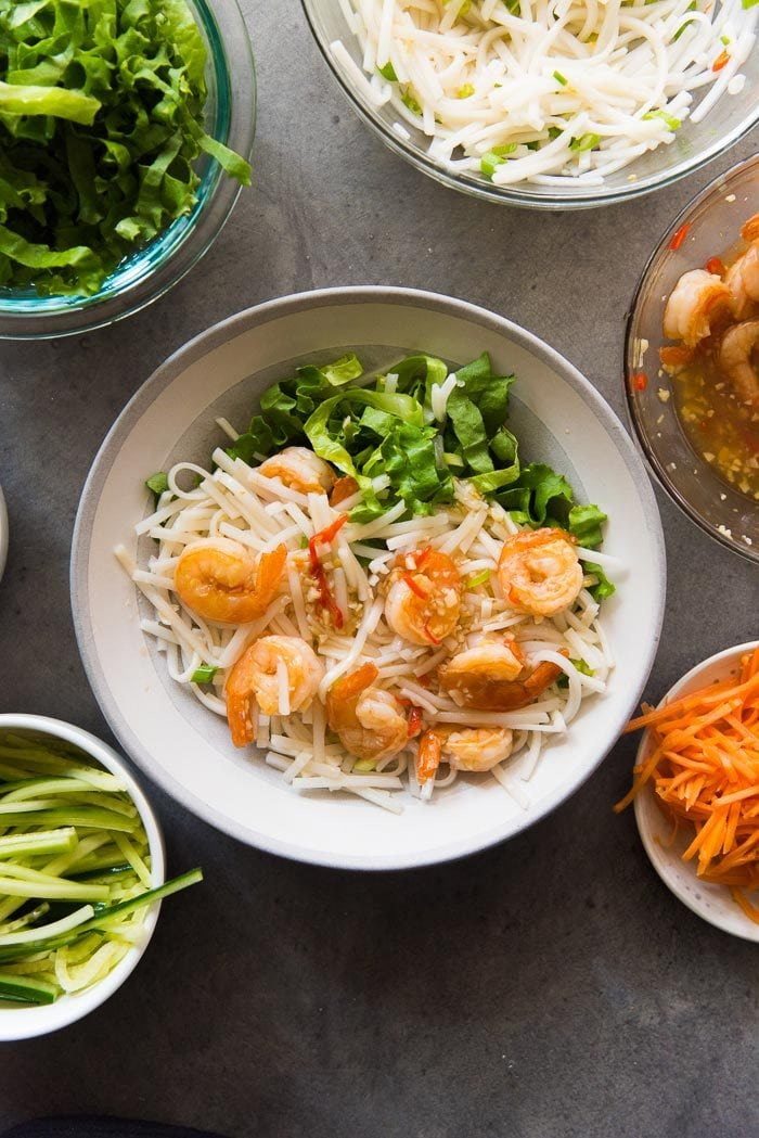 Assembling Garlic Lime Shrimp Rice noodle salad. Top the noodles with the garlic lime shrimp.