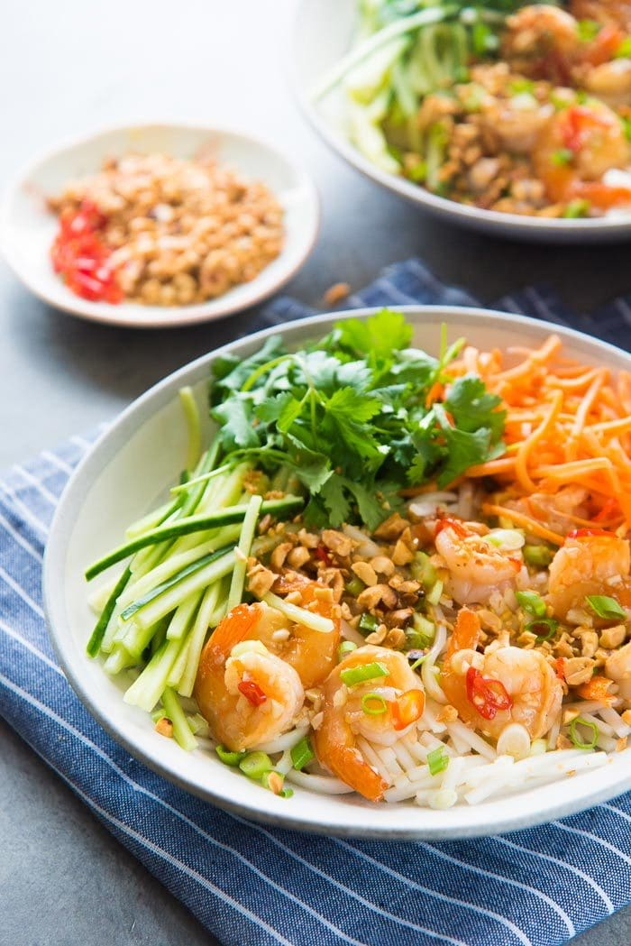 Serve the lime garlic shrimp rice noodles with crunchy cucumbers, peanuts and carrots, along with cilantro and lettuce as well. The lime garlic sauce acts as a dressing to all the vegetables.