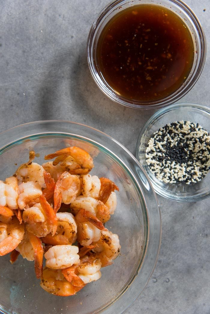 Pan fried shrimp in one bowl, with a teriyaki sauce next to it. This sauce can be used as a teriyaki shrimp marinade as well.