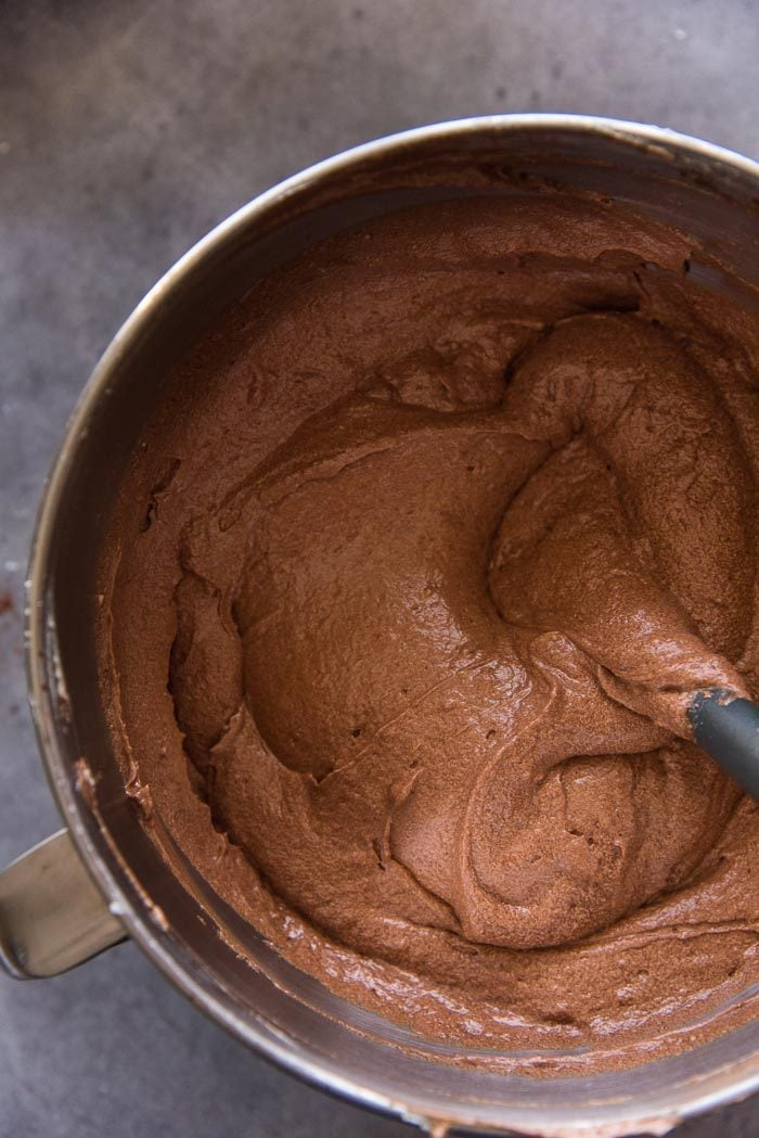 A completely mixed chocolate cake batter in the mixing bowl, with no lumps. Ready to be divided into cake pans.