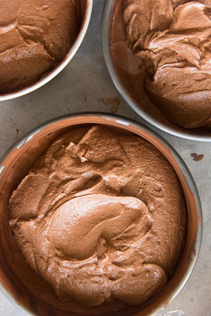 The chocolate cake batter divided into the prepared cake pans.