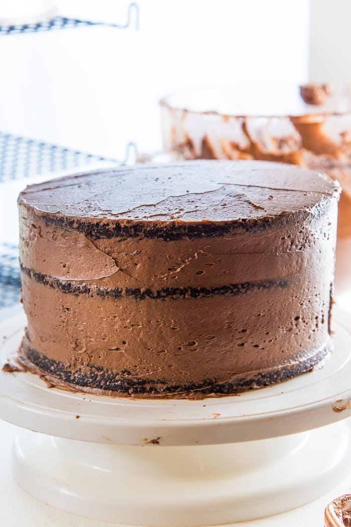 "Apply a thin coating of chocolate buttercream as a ""crumb coating"". Crumb Coating is applied to cake to even out the cake and to stick any loose cake crumbs firmly to the cake."