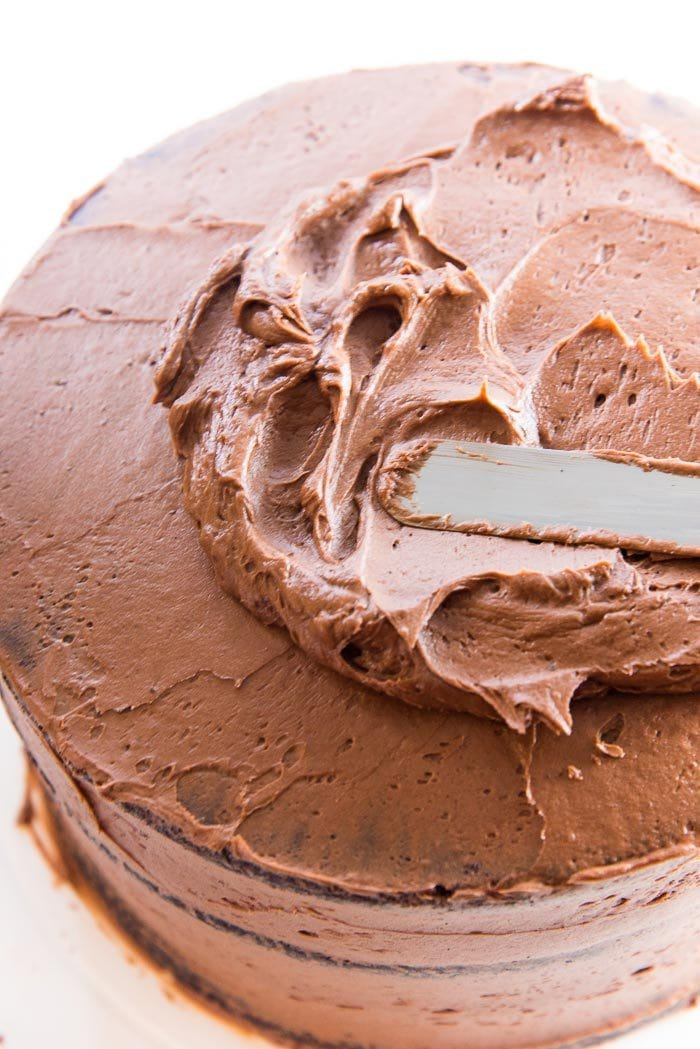 "An offset spatula swirling buttercream onto the top of the chocolate layer cake. Swirl the chocolate buttercream frosting onto the crumb coating that has been ""set"". The crumb coating will prevent any cake crumbs getting on the final frosting layer."