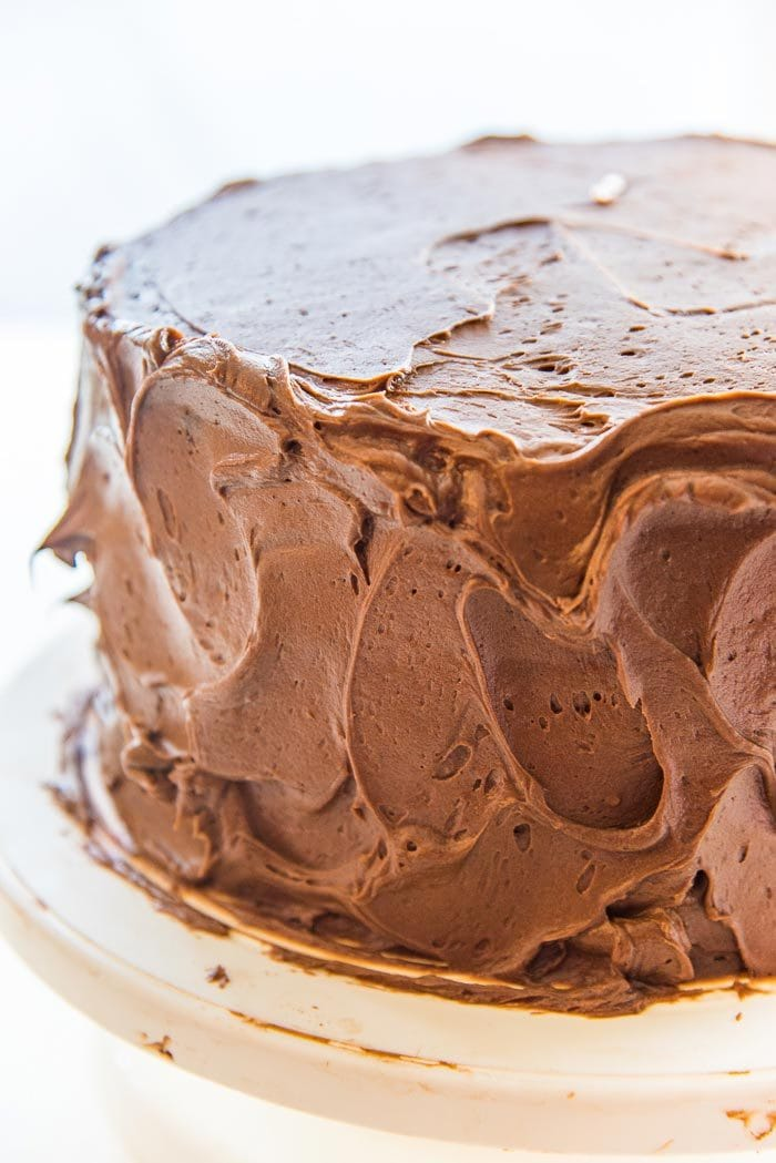 Make swirls of chocolate buttercream using an offset spatula, or the back of a spoon. A close up of the chocolate buttercream swirls on the classic chocolate cake.