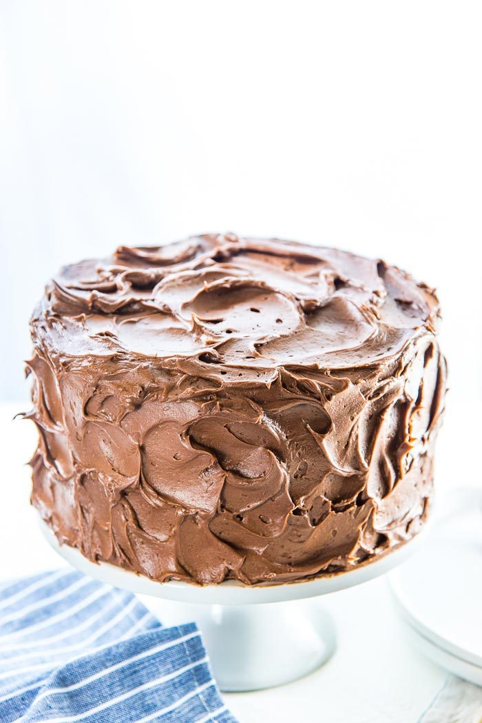 A completely frosted classic chocolate cake, on a white cake stand.
