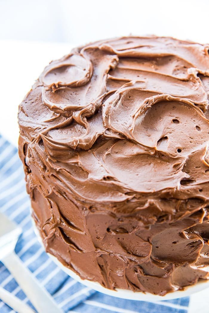 A high angle of the classic chocolate cake, showing the swirled, soft chocolate buttercream. This buttercream is creamy and buttery and easy to spread or pipe on cakes.