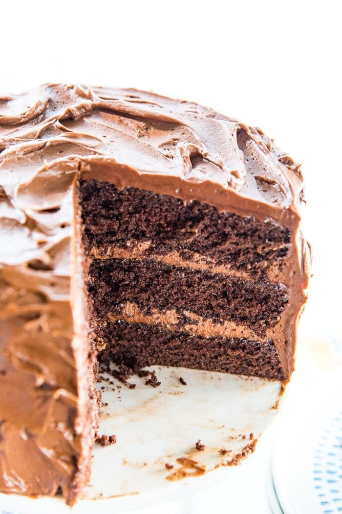 A half cut chocolate cake, showing the three chocolatey, airy, chocolate cake layers and the billowy, creamy chocolate frosting.