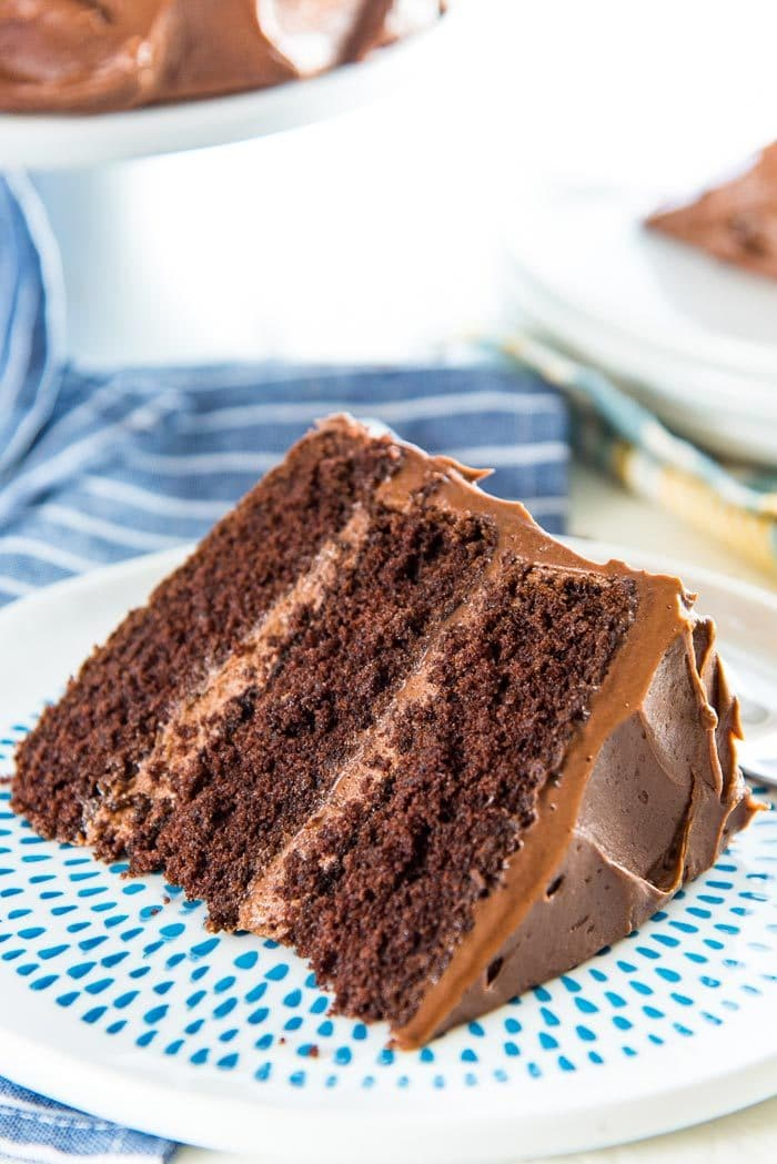 A close up of the slice of classic chocolate cake, lying on the side, on a blue spotted plate. With 3 layers of cake and a creamy chocolate frosting.