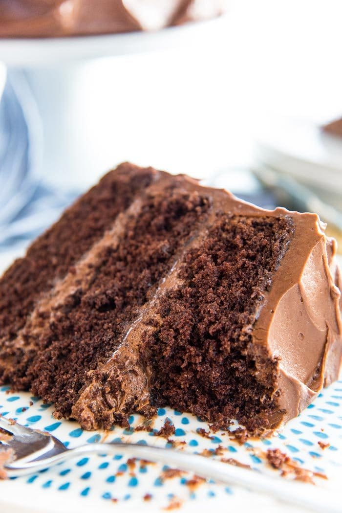 A close up of the Classic Chocolate Layer Cake with creamy chocolate buttercream, and soft, airy chocolate cake layers.