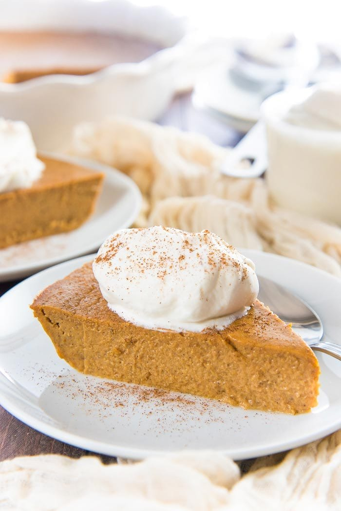 A close up of the side view of the gluten free pumpkin pie slice showing how creamy the filling is. Served with whipped cream on top.