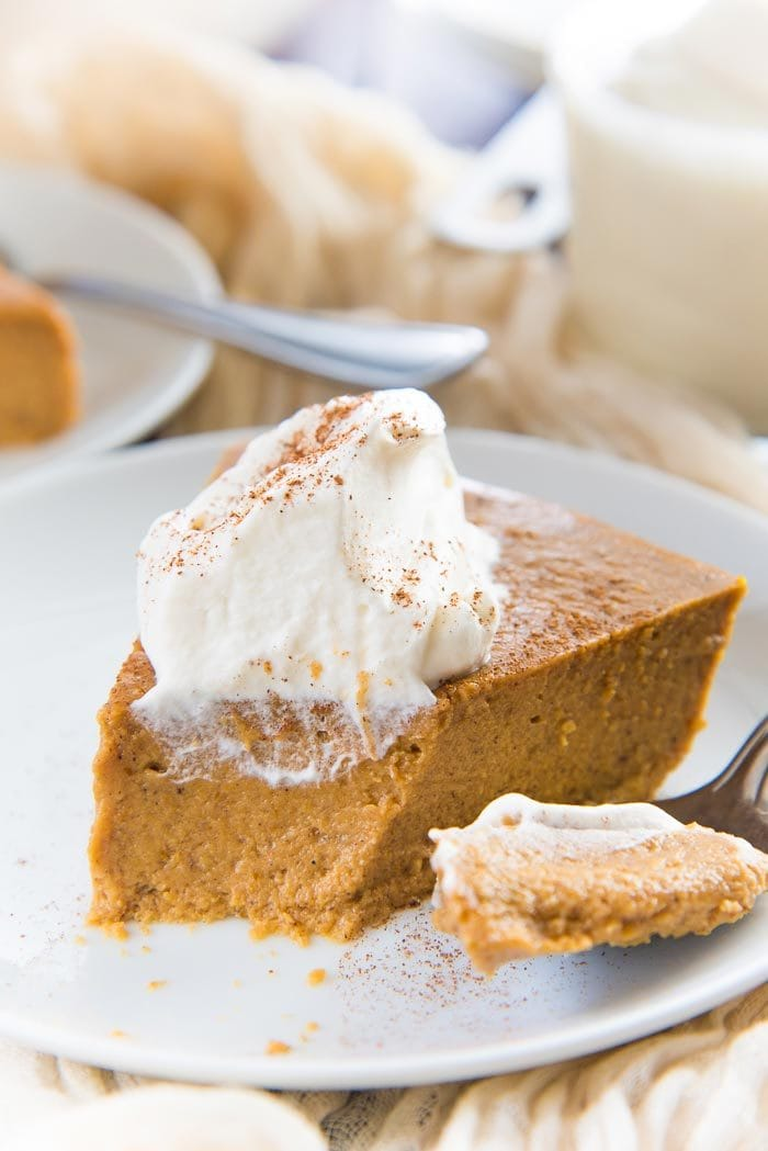 A close up of the inside of the crustless pumpkin pie pudding slice with whipped cream on top. The filling is creamy, smooth, and has no weeping or curdling.