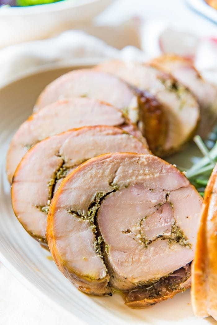 Sliced oven roasted turkey roulade, with a herb rub in the middle, fanned out on a white serving tray.
