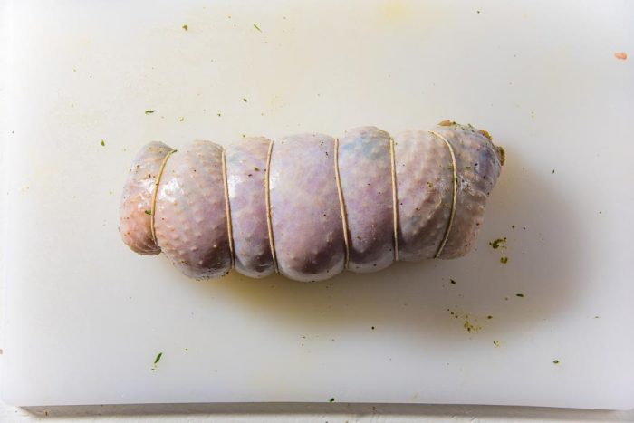 Sous vide turkey roulade rolled up and tied with twine.