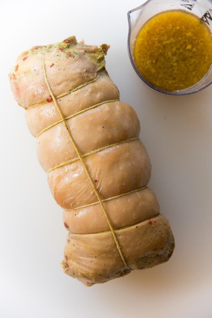 Sous vide cooked turkey roulade on a white board. The turkey skin is still pale and needs to be cooked separately. The pan drippings are in a separate jug.