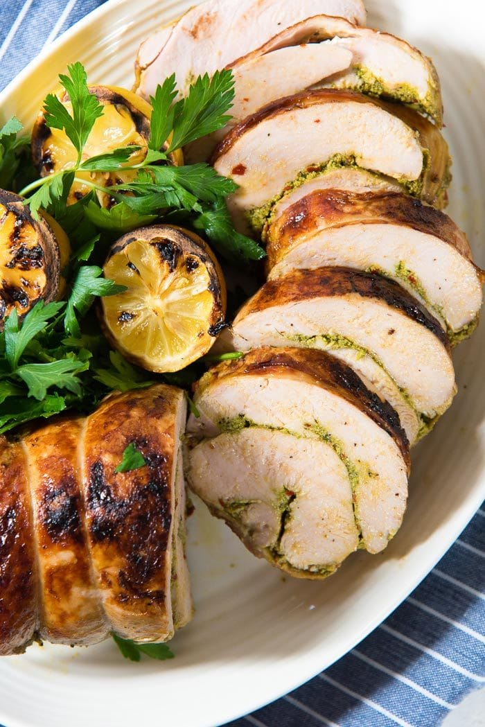 An overhead view of the sliced sous vide thanksgiving turkey roulade on a serving platter with grilled lemons and herb garnishes.