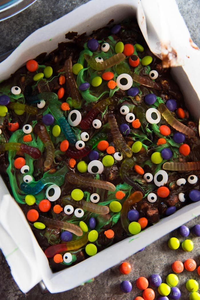 Halloween rocky road slices decorated with halloween candy in a lined square pan, ready to be chilled.