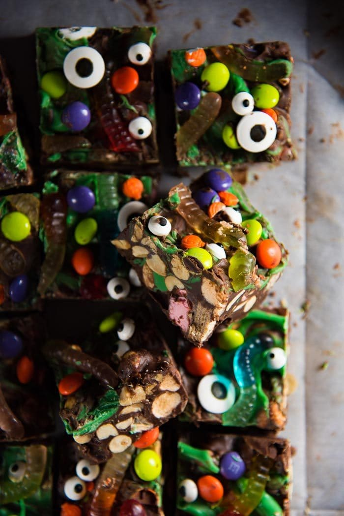An overhead view of Halloween Rocky Road Slices decorated with halloween treats. Easy, no bake, cute halloween treats perfect for parties. Slices of rocky road studded with marshmallows, peanuts, candy bars, gummy worms and M &Ms.