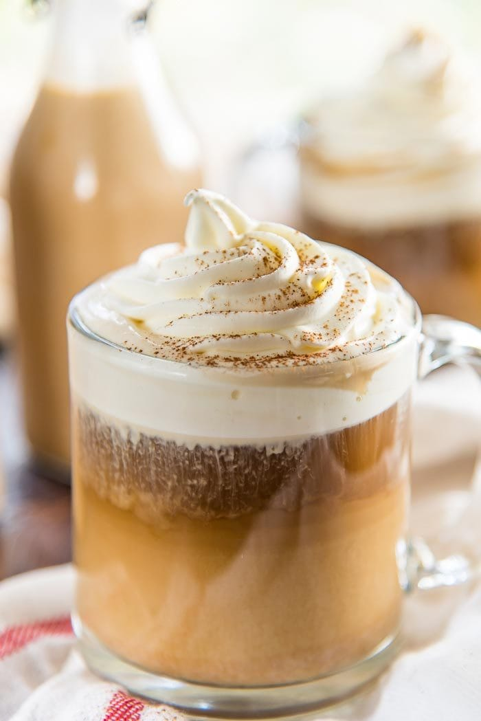 A close up of the pumpkin spice latte in a glass mug, with the creamer and the coffee topped with the whipped cream swirl on top.
