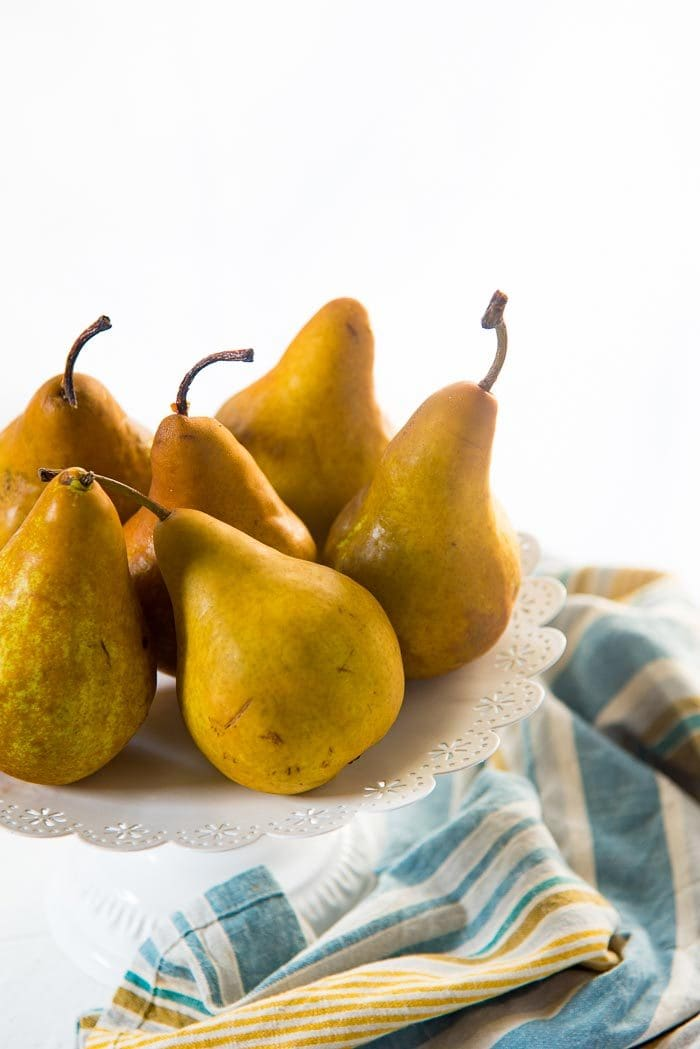 Six Bosc Pears on a white cake stand with a blue green napkin in the background.