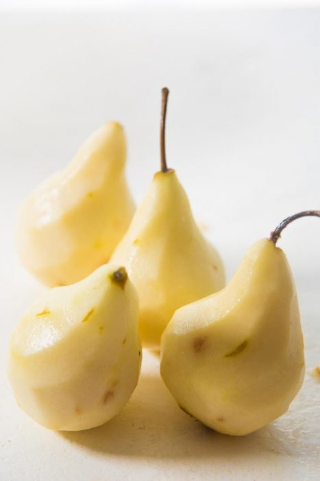 Four Peeled bosc pears on a white tabletop.