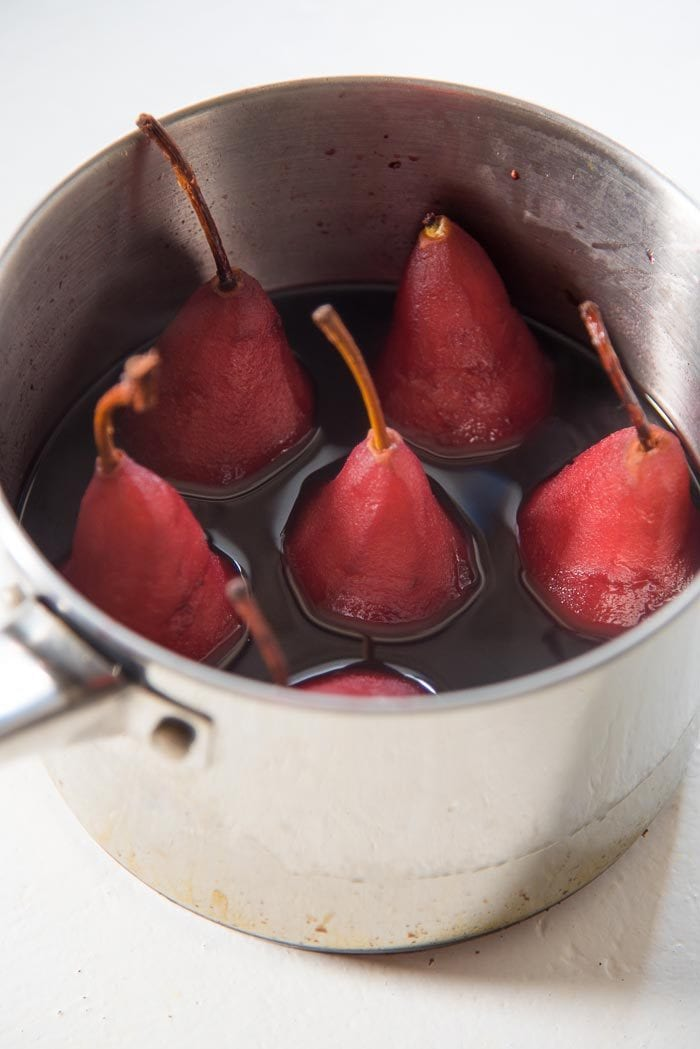 Red Wine poached pears in the red wine liquid, cooling in the saucepan.