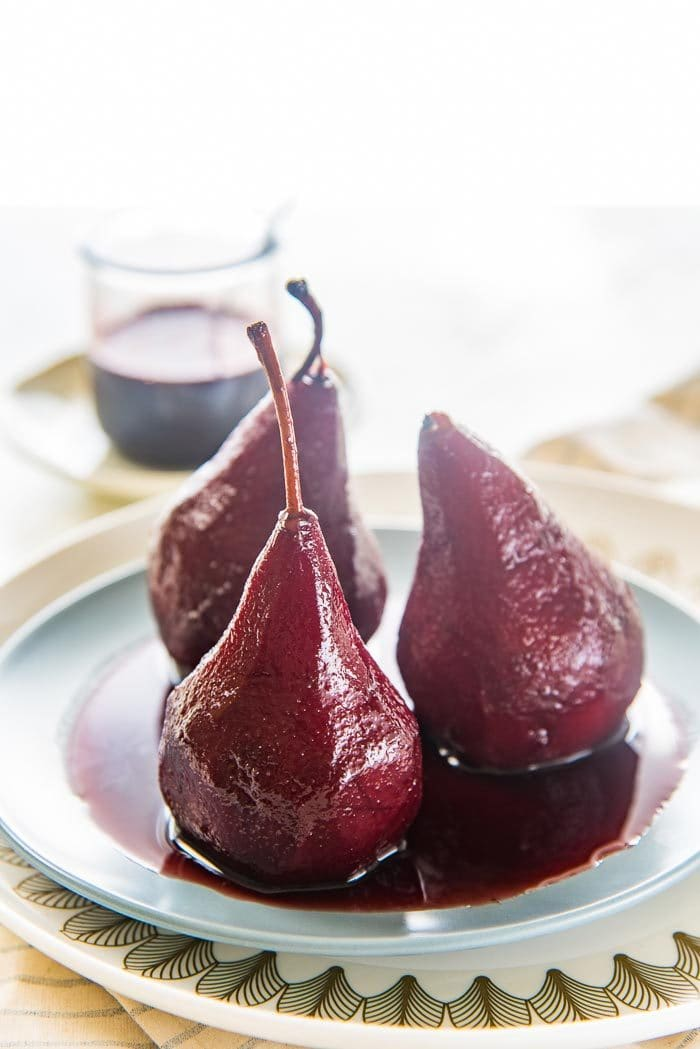 three red wine poached pears on a blue plate with red wine syrup, with extra red wine syrup in the background.